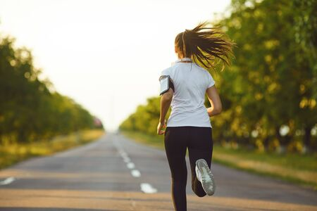 One active female runner running jogging on road in the morning. Active lifestyle. 스톡 콘텐츠