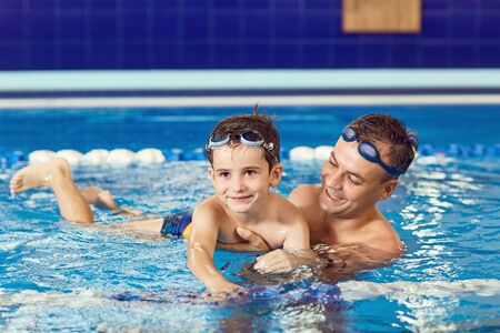 Father and son swim in a swimming pool.