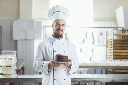 Confectioner smiling man holding cake smiling in a pastry shop Stockfoto - 127794848