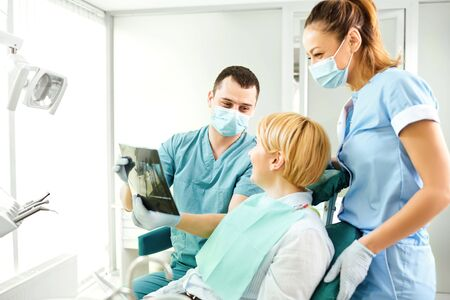 Dentist shows a x-ray image of a girl patient in the dentists office.