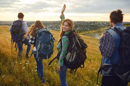 Young people with backpacks stand in the forest from behind. Tourists on the tourist route. Stockfoto