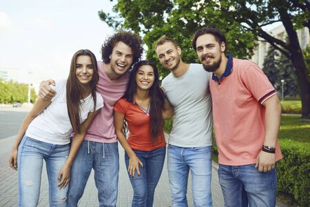 Group of people smiling while standing on a city street in summer. Friends hugging at a meeting.
