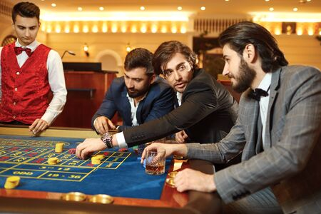 Group man gambler friends in a suit is sitting at table roulette playing poker at a casino.