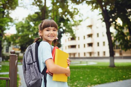 Happy little student girl with a backpack on her way to school. First day to school. Back to school. Stockfoto - 127794858