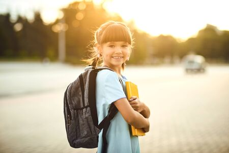 Happy little student girl with a backpack on her way to school. First day to school. Back to school. Stockfoto - 127794859