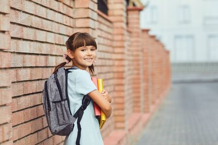 Girl schoolgirl looking with a backpack and books in hand goes to school.