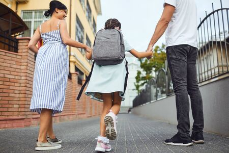 Family and litle girl student with a backpack on a city street. Mother and father hold their daughter with a backpack by the hand on the way to school. First day to school. Back to school.