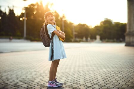 Happy little student girl with a backpack on her way to school. First day to school. Back to school.