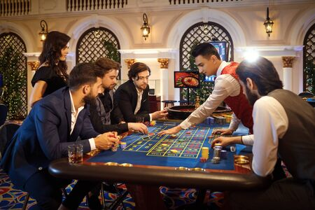 People make bets gambiling at the roulette table in the casino. Gambling in a casino. 스톡 콘텐츠