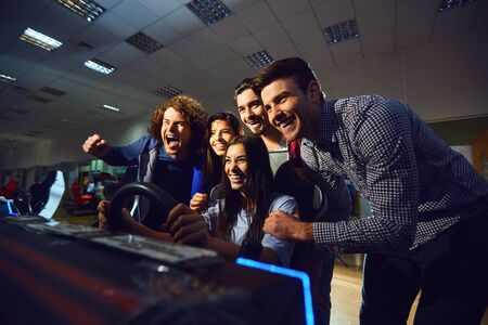 A group of friends playing arcade machine. in an amusement park. Young people have fun. Banco de Imagens - 131889847