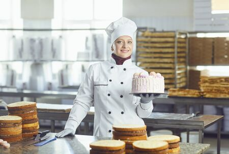 Woman confectioner with pastry cake in his hand smiling at the bakery. Banco de Imagens