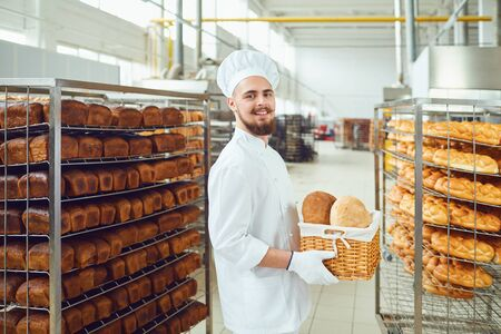 Bearded baker smiles holding a basket of bread at the bakehouse.