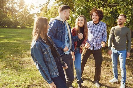 Young people laugh while standing in a park in spring. Friends have fun in their free time. Banco de Imagens - 131889831