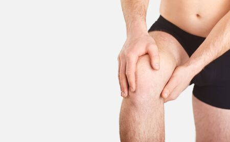 Trauma, pain, knees. Ligament rupture. Rupture of the meniscus. A man in underwear holds his knee with a hand on a gray background. Banco de Imagens