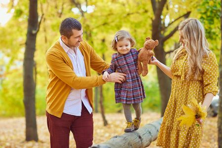 Stylish young man and woman holding hands of little daughter helping her to walk on wood fence in park Banco de Imagens