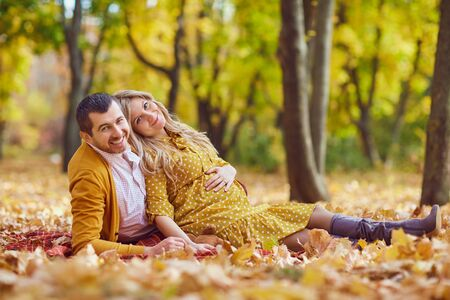 Couple sitting on yellow leaves in autumn park. Banco de Imagens - 131890331