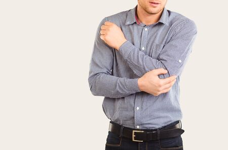 Elbow injury. Pain in the elbow. A man holds an elbow with his hand on a gray background. Banco de Imagens