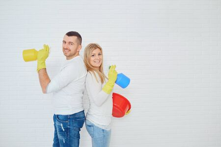 Beautiful young family couple sharing household chores cleaning on white background. Banco de Imagens
