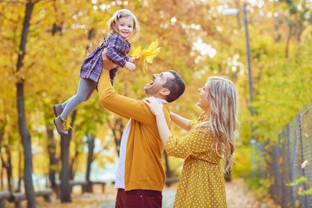 Side view of happy man tossing up adorable girl with charming blond woman standing near in autumnal park