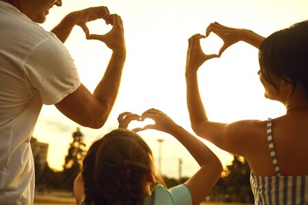 Happy family concept. Hands of family group people in the shape of a heart against the sunset.