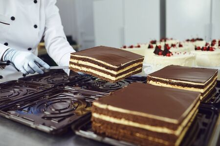 The hands of a pastry chef pack a cake on a table with other cakes in the bakery. Banco de Imagens - 131890411