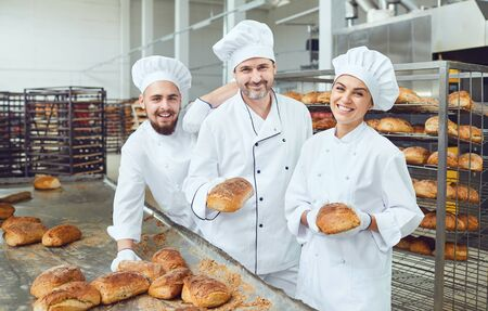 Beautiful bakers smiling holding fresh bread in their hands in a bakery factory