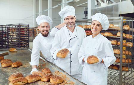 Hermosos panaderos sonriendo sosteniendo pan fresco en sus manos en una fábrica de panadería
