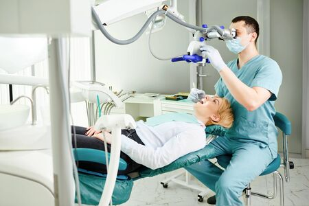 Male dentist looking through a microscope at a girls teeth patient in a dental clinic.