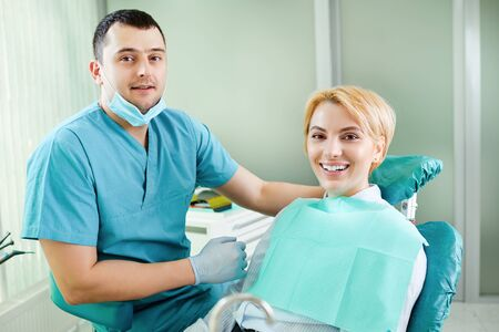 Dentist and patient are smiling in the dentists office. Stock Photo
