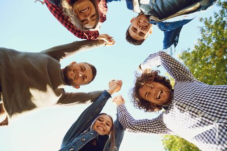 From below shot of content friends standing in circle with hands up looking at camera with excitement under blue sky Stockfoto