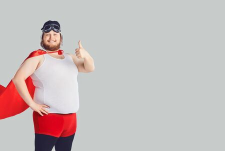 Funny fat man in a superhero costume raised thumb up on a gray background. Stockfoto