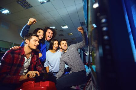 A group of friends playing arcade machine. in an amusement park. Young people have fun. Stockfoto