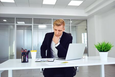 Serious blond businessman thinks sitting at a table at a workplace in an office. Stockfoto