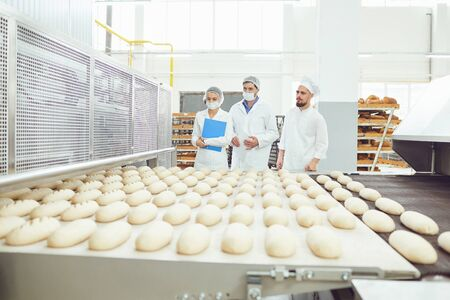 Technologist and baker inspect the bread production line at the bakery. Stockfoto