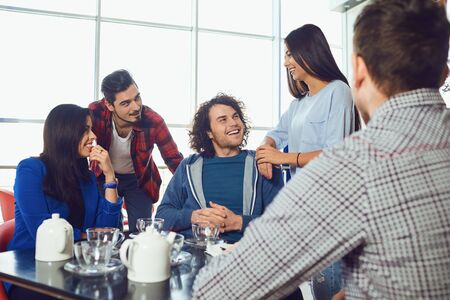 Funny friends talk and laugh in a cafe. Young people smiling indoors. Stockfoto