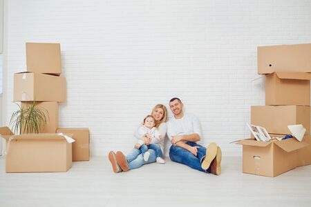 Happy couple unpacking cardboard boxes at new home at moving day. Stockfoto