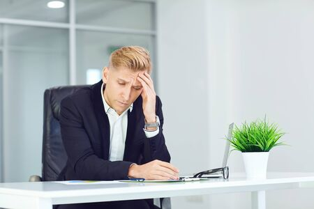 Unhappy,headache,upset, sick businessman holds his head with his hand while sitting at a table in the office. Stockfoto