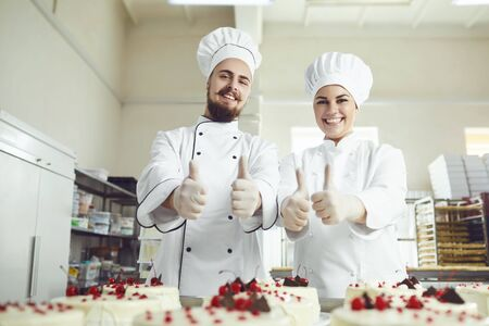 Two confectioners in white uniform smiling raised their thumbs up at the workplace in the bakery.