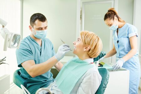 Dentist checks the teeth of the patient girl sitting in the dentists chair. Stockfoto