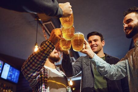 Young people clink glasses with beer in a bar. Young people in a meeting in a pub. Stockfoto