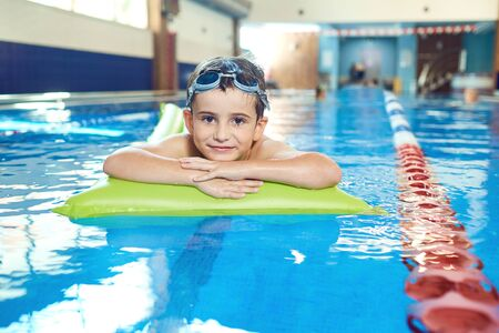 The boy smiles in the swimming pool indoors. Stockfoto