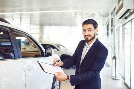 A car dealer is holding documents on the sale of a car. Auto business concept.Buying rental a car.