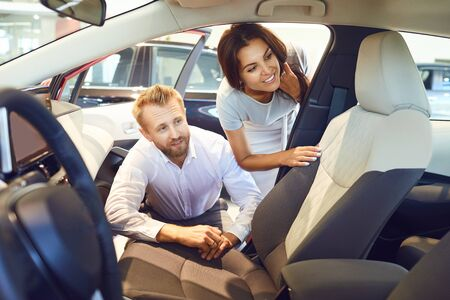 Young couple choose a new car in showroom. Buying and renting cars. Stockfoto