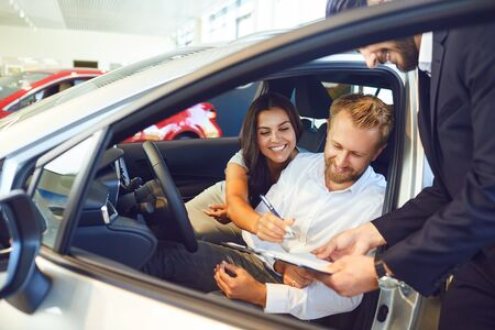 A couple buys a car in a car showroom. A man signs a car rental agreement.