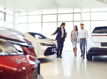 Happy couple and the dealer selling cars look the car in the showroom. Buying rental a car. Stockfoto