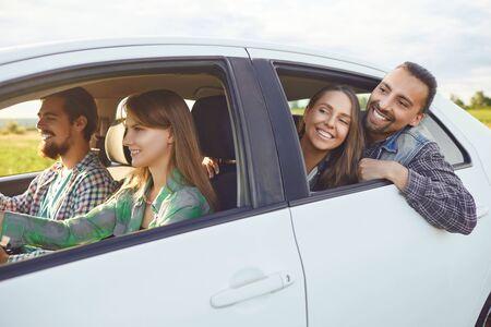 Un grupo de amigos felices los viajeros están conduciendo en un automóvil en la carretera.