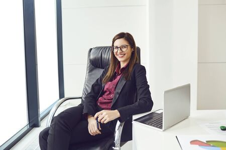Portrait of a young businesswoman with glasses sitting at a table in a modern office.