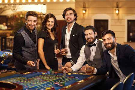 A group of friends are looking into the camera at the casino roulette table. Gambling in a casino.