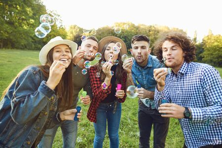 Group of young stylish men and women blowing soap bubbles at camera having fun in green park Stockfoto