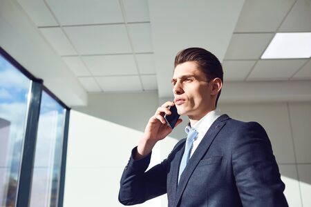 Young businessman in a suit talking on the phone in the office.